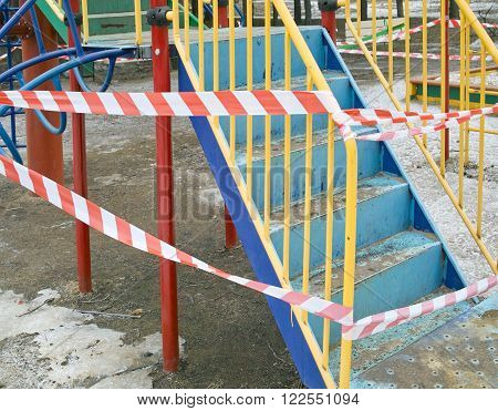 A playground with a warning tape around cropped outdoor shot concept of a danger