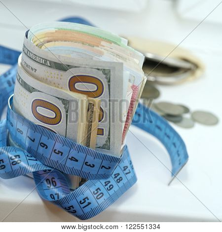 Bundle of US dollars wrapped with a blue measure tape concept of wealth and success. Macro shot with particular focus