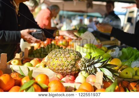 Buyer shopping for groceries. Pineapple with fruits on grocery market stall background