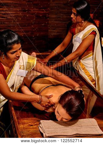 Woman having ayurvedic massage with pouch of rice. Passage to India. Four hands massage.