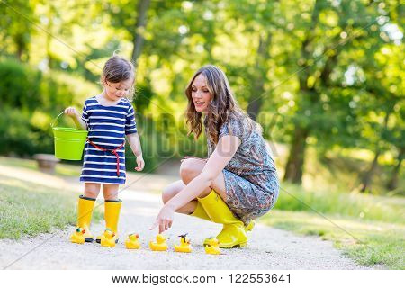 Mother and little adorable daughter in yellow rubber boots, family look. Woman and little kid girl playing with duck toys in summer park