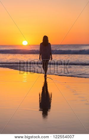 Woman walking on sandy beach in sunset leaving footprints in the sand. Beach, travel, concept. Copy space. Vertical composition.