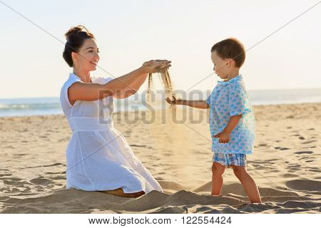 Happy family - mother and small baby son sit on sunset sea beach and play with sand slipping through woman hand fingers. Active parents and people outdoor activity on summer vacations with children.