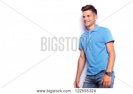 side portrait of casual young man in blue polo shirt and jeans posing standing while looking away in white isolated studio background
