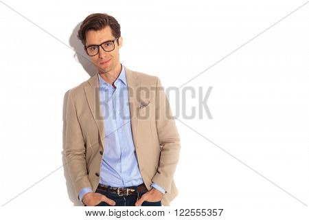 portrait of fashion guy wearing glasses, posing with both hands in pockets while smiling at the camera in isolated studio background