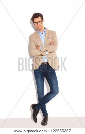 portrait of smart casual man wearing glasses, posing in white studio background with hands and legs crossed