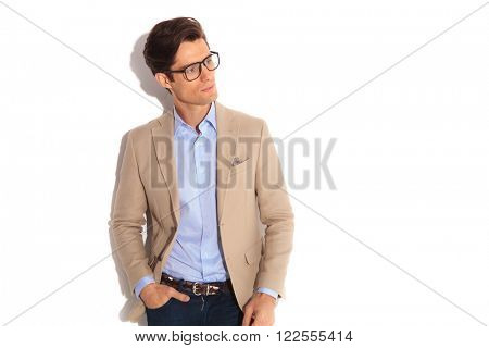 portrait of handsome man wearing glasses while posing with hand in pocket, looking away from the camera in isolated studio background
