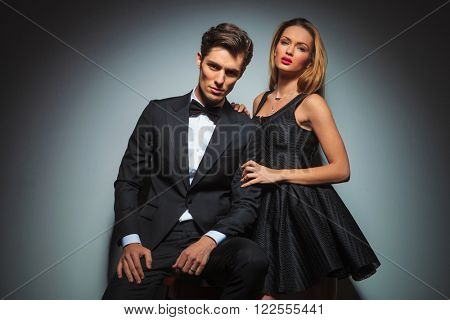 elegant couple in black posing in studio background looking at the camera. man is seated while woman stands by his side with hands on his shoulder and arm