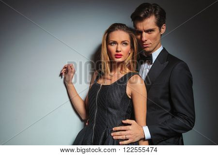 elegant businessman in black suit looking at the camera while embracing woman from behind. woman raise hand while looking away in gray studio background