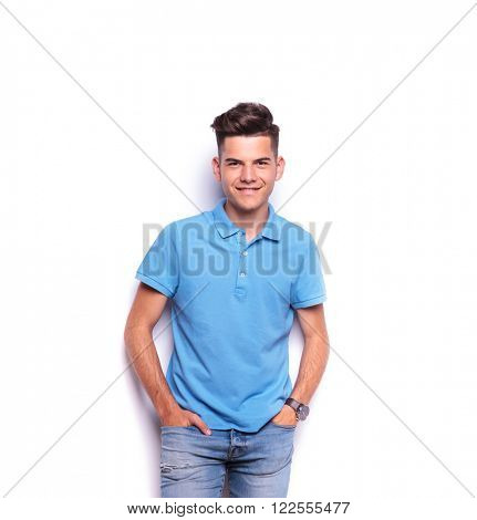 casual boy in blue polo shirt posing with both hands in pockets while looking at the camera in white isolated studio background
