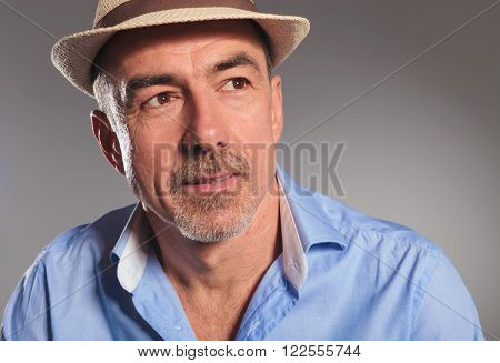 closeup portrait of mature man wearing open shirt and brown hat looking away from the camera in gray studio background