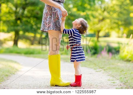 Young mother and little adorable child girl in rubber rain boots having fun together, family look. Little girl in red boots. Long legs of woman.