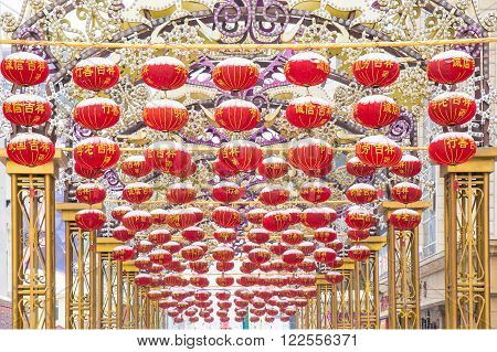 Harbin, China 01/19/2016 Alley with golden pillars , dozens of red lanterns covered with snow and chinese charaters wishing luck and fortune Chinese new year celebration decoration