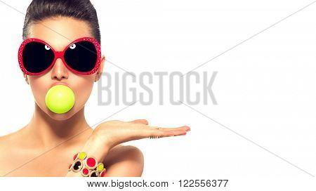 Beauty summer fashion model girl wearing sunglasses with green bubble of chewing gum and bright makeup showing empty copy space on the open hand palm for text over white background. Beautiful woman