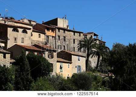 Monte Carlo, Monaco - September 20, 2015: stone houses aged residential buildings green trees on mountain top against clear blue sky day time on landscape background, horizontal picture