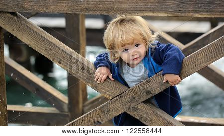 Baby Boy Behind Wooden Fence