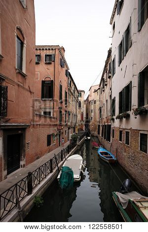 Venice Italy - September 22 2015: venetian canal narrow street between old aged residential buildings and boats at moorings in sea lagoon on townscape background vertical picture