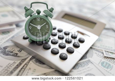 Calculator and alarm clock on money concept for time is money or tax and savings deadline