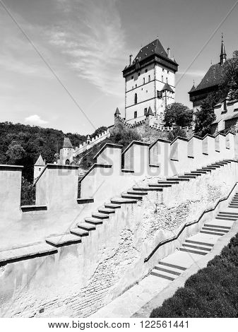 Karlstejn Royal Castle, medieval gothic castle with fortification walls on sunny summer day. Czech Republic. Black and white image.
