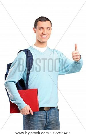 A Male Student Holding A Book And Giving Thumb Up