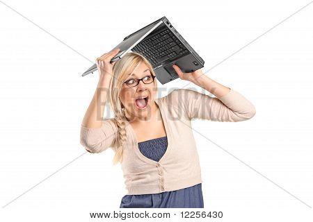 Una mujer asustada que cubre su cabeza con un ordenador portátil