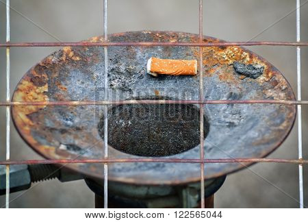 Closeup of a cigarette butt and rusty metal ashtray