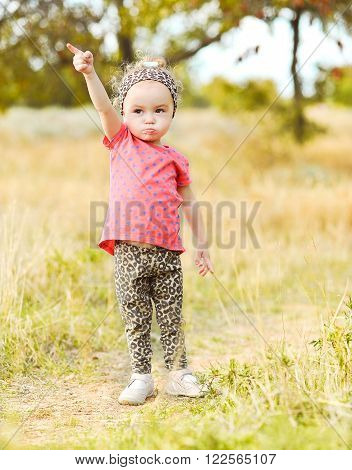 Baby girl putting forefinger up,showing something outdoors. Wearing stylish leopard pants and headband. Walking in park. Childhood.