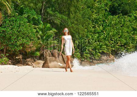 Woman wearing dress on beach Anse Intendance at Seychelles, Mahe