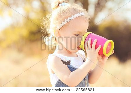 Young baby 2-3 year old girl drinking with plastic cup outdoors. Wearing stylish dress and accessories.