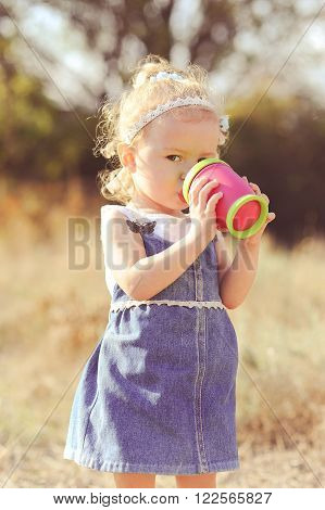Baby girl 2-3 year old drinking water from plastic cup outdoors. Wearing stylish denim dress. Childhood.