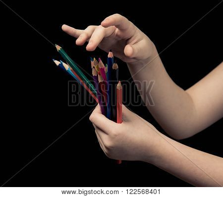 Child's Hands With Colored Pencils On Dark Background