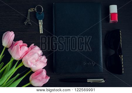 Women's pink and black accessories on dark wooden background with bouquet of tulips. Business woman concept. Fashion style on the work. Congratulate. Flat lay.