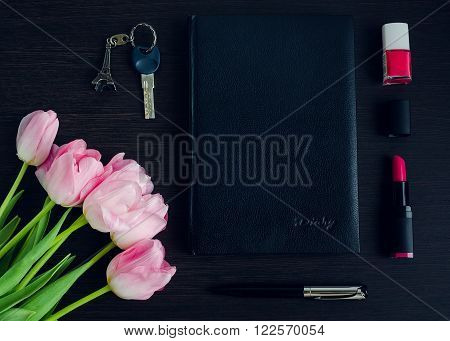 Woman's pink and black accessories on dark wooden background with bouquet of tulips. Business woman concept. Fashion style on the work. Flat lay.