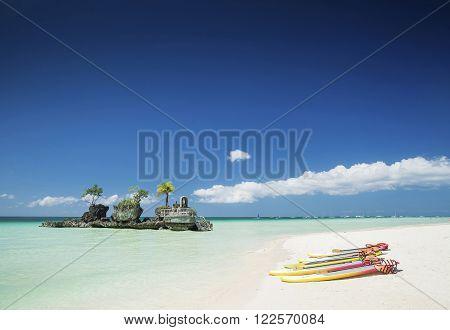 tropical beach christian shrine and tourist canoes on boracay island philippines