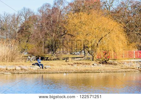 Kalmar Sweden - March 17 2016: Male person sit by the water with a meal in his hand and a bike behind him. He is resting and looking at the birds in the sea. Real people in everyday life.
