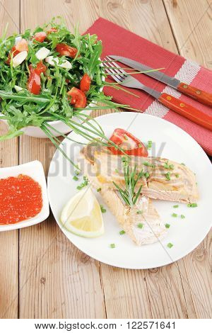 healthy fish cuisine : grilled pink salmon steaks with red caviar in white bowl , lemon and vegetable salad on white dish with cutlery and pepper grinder over wooden table