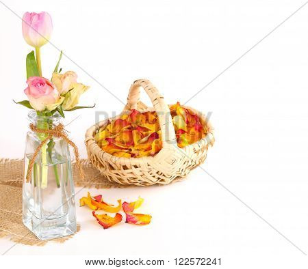 three pink roses and a basket of dried petals of roses