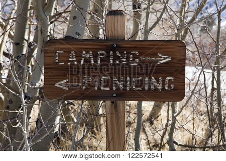 Wooden camping and picnicing sign with arrows