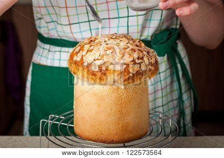 A Woman Wearing Apron Dizzling Easter Bread (Kulich) with Sugar Icing