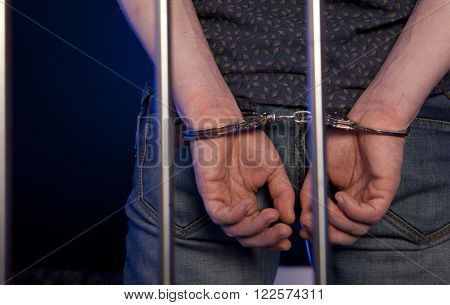 Hands of the prisoner on a steel lattice. Arrested man in handcuffs