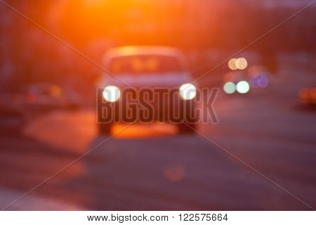 Blurred silhuette of a car at sunset