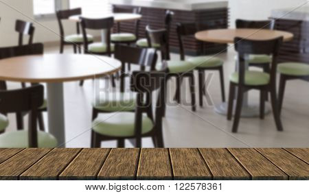 green leather cushion on wooden chair in food court (blur background with wood table top for display or montage your product)