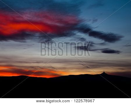 Dramatic sunset sky with colorful clouds and silhouette of Jested ridge, Liberec