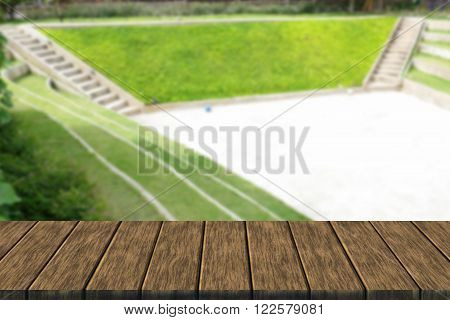 tiered seat of the amphitheater and outdoor stage (blur background with wood table top for display or montage your product)