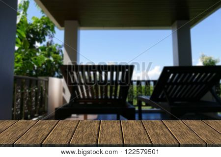 wooden deckchair at the balcony and terrace with forest and sky view (blur background with wood table top for display or montage your product)