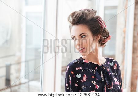 Smiling beautiful young woman with curlers standing near the window