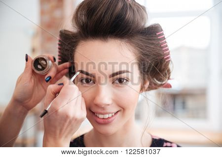 Makeup artist doing makeup to happy pretty young woman with curlers