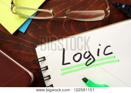 Logic written in a notepad on a wooden background.