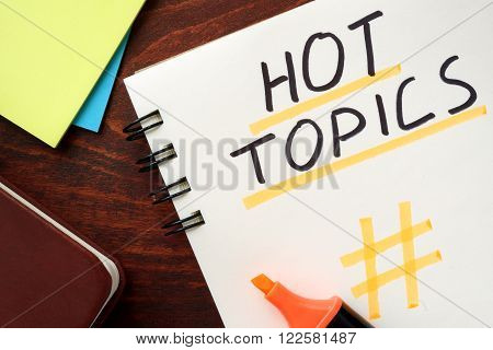 Hot Topics written in a notepad on a wooden background.