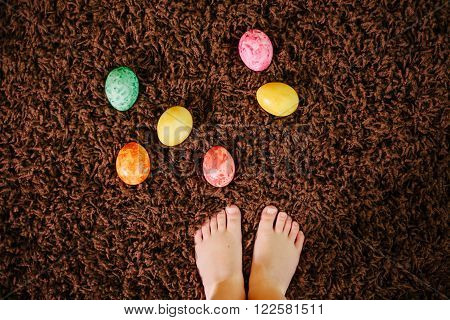 girl standing near Easter eggs. top view flat lay.feet. legs